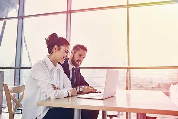 Homme d'affaires et femme d'affaires travaillant avec un ordinateur portable au bureau